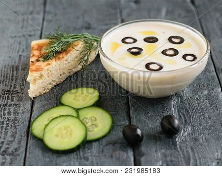 Tzatziki Sauce In A Glass Bowl On A Dark Wooden Table With A Piece Of Bread. Vegetarian Greek Cuisin