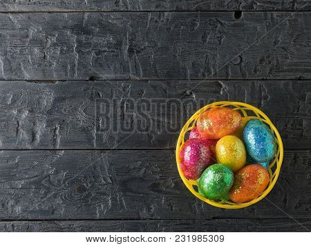Basket With Colorful Eggs On A Black Rustic Table. Decorations For The Easter Table. The View From T
