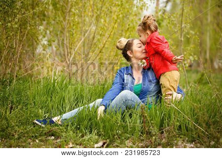 Family Time. Mother Is Sitting On The Lawn. A Little Daughter Kisses Her On The Forehead. Spring Wal