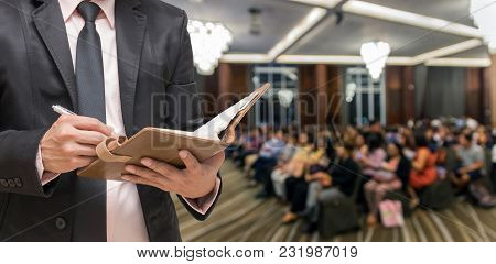 Businessman Writing The Notebook On The Abstract Blurred Photo Of Conference Hall Or Seminar Room Wi