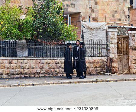 JERUSALEM, ISRAEL - DECEMBER 29, 2016: Three Hasidim talk near Mea Shearim quarter one of oldest districts in Jerusalem. quarter was founded in 1874 by Zalman Baharan and Joseph Rivlin