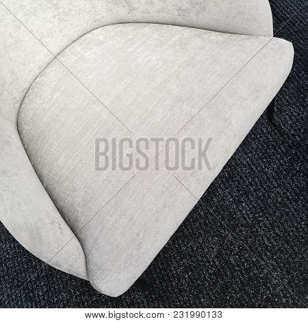 Empty Seat Of A Simple Gray Armchair On Dark Carpet Floor.