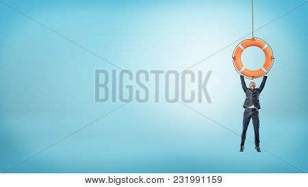 A Tiny Businessman Holds On To A Giant Orange Life Buoy With Both Arms On A Blue Background. Life Sa