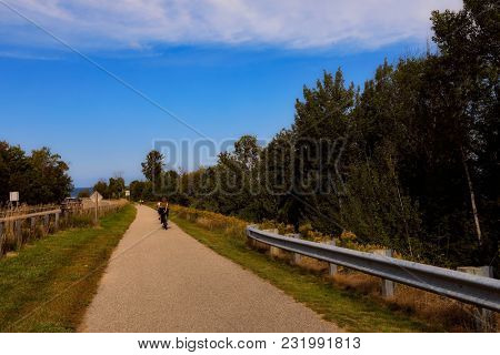 Charlevoix Michigan on Lake Michigan is a beautiful vacation destination.  A bike and running trail connects this city to popular Petoskey. A biker is on the path.