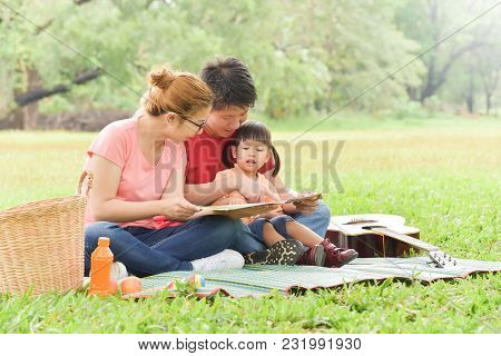 Happy Young Asian Family With Their Daughter Reading A Book. People Having Fun In Nature At Park Out