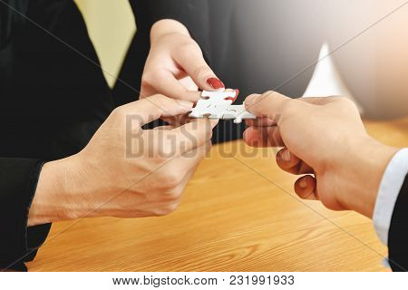 Group Of Business People Hands Are Holding And Conecting Jigsaw Puzzle On Desk And Solving Puzzle To