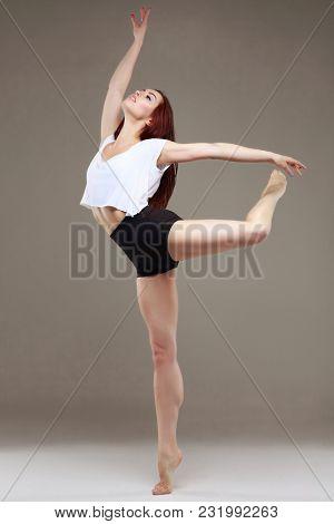 Beautiful ballet-dancer, modern style dancer posing on studio background. Contemporary