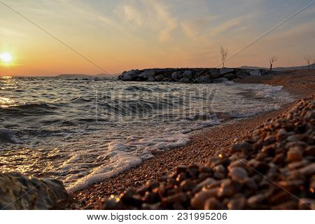 Small Waves Coming Into The Shoreline During Golden Hour Along The Coast.a Bold And Dramatic Scene O