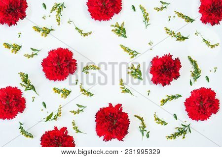 Floral Pattern Made Of Red Carnations, Green Leaves, Branches On White Background. Flat Lay, Top Vie