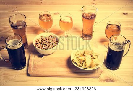 Beer Mugs, Glasses And Beer Snacks On Wooden Table. Selective Focus. Vintage Style.