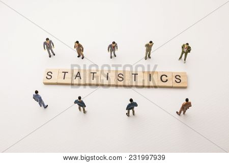 Miniature Figures Businessman : Meeting On Statistics Letters By Wooden Block Word On White Paper Ba