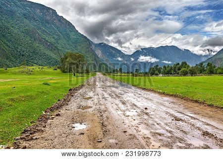 Wet Dirt Road And Tree In The Valley Against The Backdrop Of Mountains And Clouds In The Rain In Sum