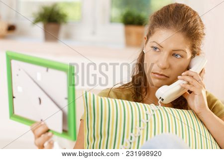Relationship problems. Sad young woman calling boyfriend on phone, holding a framed picture.