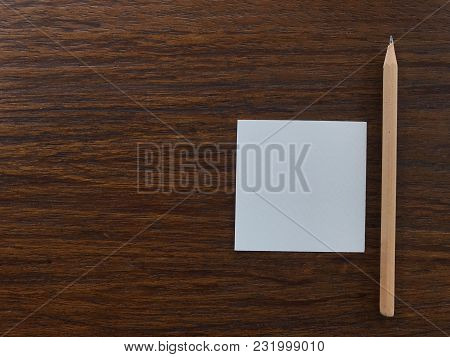 Natural Brown Wood Pencil And White Blank Paper Putting On Dark Brown Wood Table With Copy Space On