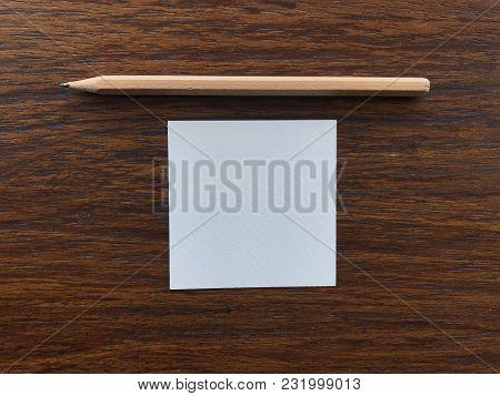 Natural Brown Wood Pencil And White Blank Paper In Square Shape Putting In The Middle Of Dark Brown