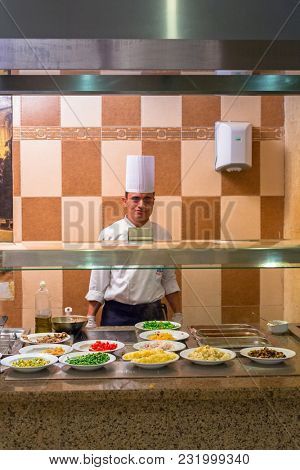 HURGHADA, EGYPT - APR 15, 2013: Cook serving breakfast at Three Corners Sunny Beach hotel in Hurghada. Three Corners is Belgian company with 11 hotels at Red Sea in Egypt and one in Budapest, Hungary.