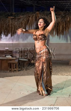 Hurghada, Egypt - April 16, 2013: Unidentified belly dancer doing performance in small village on the desert at Hurghada, Egypt. This show is one the of main attractions in Egypt.