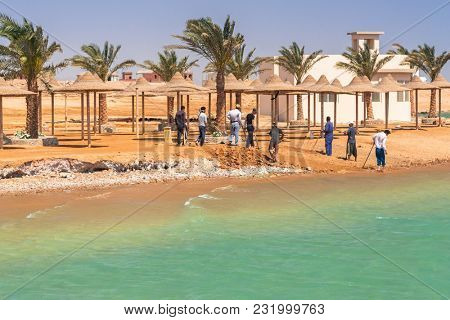 Hurghada, Egypt - April 17, 2013: Workers fixing coastline of tropical resort near Hurghada, Egypt. Hurghada is very popular tourist destination in Egypt.