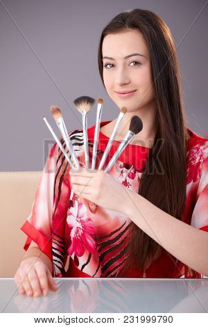 Beautiful young woman holding make-up brushes, looking at camera, smiling.