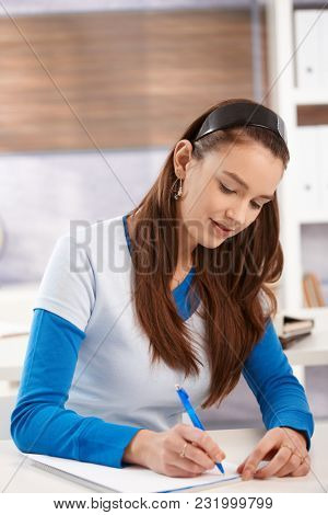 Attractive young girl sitting at desk, writing in exercise book, looking down, smiling.
