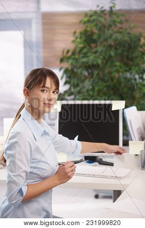 Portrait of happy young woman working at office. Young female office worker working with computer, smiling.
