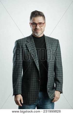 Happy older businessman with gray hair in business casual, smiling.