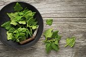 Fresh spinach leaves in bowl on rustic wooden table. poster