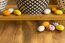 Easter Candy Eggs On Wooden Surface Besides Withe Bowls With Black Pattern