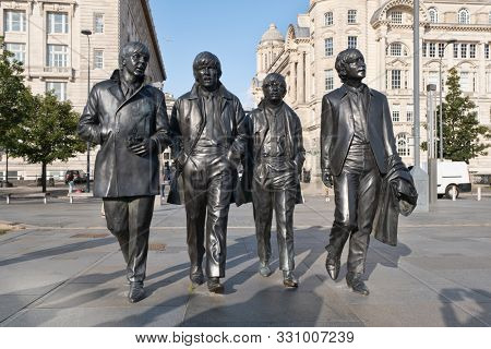 LIVERPOOL,UK - AUGUST 5,2019 : Iconic bronze statues of the four Beatles in front of the Mersey waterfront in Liverpool
