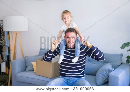 Young handsome father holding his beautiful toddler child daugther at shoulders