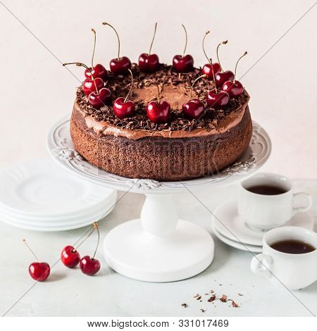 Chocolate Cake On A Cake Stand Decorated With Chocolate Shavings And Sweet Cherries, Square