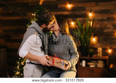 Guy Kisses His Girlfriend By The Christmas Tree. Young Man Gives New Year Present To His Girlfriend.