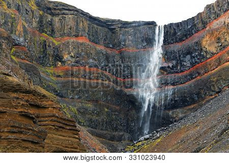 Hengifoss Waterfall, the third highest waterfall in Iceland is surrounded by basaltic strata with red layers of clay between the basaltic layers