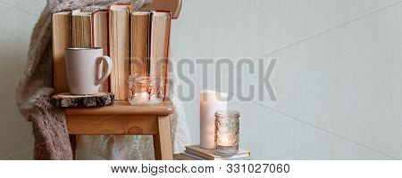 Hygge And Cozy Home Concept - Books, Cup Of Coffee Or Hot Chocolate And Candles, Seasonal Autumn Fal
