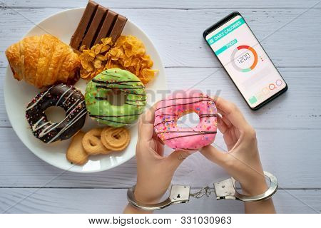 Calories Control, Food Diet And Weight Loss Concept. Top View Of Two Hands Was Control By Handcuff,
