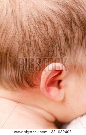 Newborn baby ear covered with thin downy hair known as Lanugo symptom