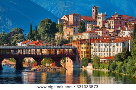 Bridge Ponte degli Alpini at river Brenta Bassano del grappa Italy. Panoramic view at old town with vintage building and tower and wooden bridge at background Alpine mountains scenic landscape.