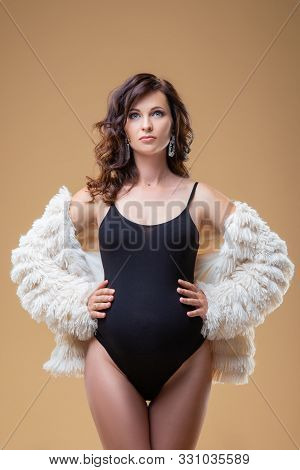 Young Brunette Pregnant Woman In Fur Coat On A Plain Background. Beautiful Stylish Healthy Pregnancy