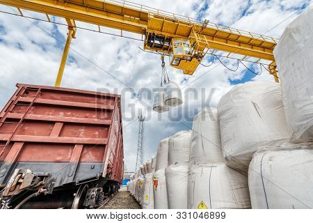 Cargo Crane Lifts Two Large Bags Of Ammonium Nitrate. Big Yellow Gantry Crane. The Work Of Lifting E