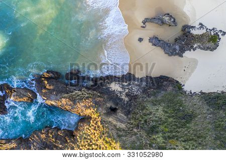 Waves Wash Onto The Beach And  Into An Eroded Rock Tunnel In The Cliffs Of The Headland. High Above