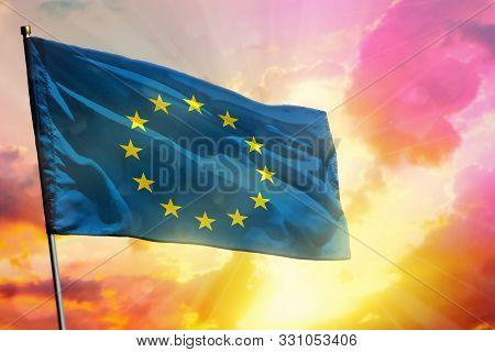 Fluttering European Union Flag On Beautiful Colorful Sunset Or Sunrise Background. European Union Su