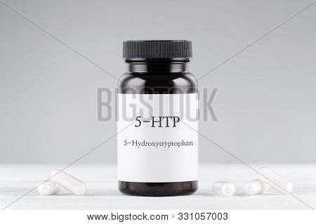 Nutritional Supplement 5-htp Hydroxytryptophan, Bottle And Capsules On Gray