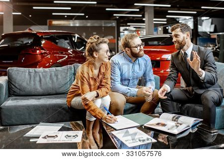 Young Couple With Sales Manager On The Comfortable Couch At The Car Dealership. Young Family Buying
