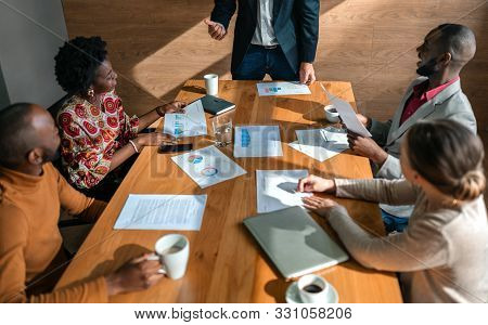 Close Up Of Boardroom Meeting. Multi Ethnic Coworkers In Business Strategy Meeting