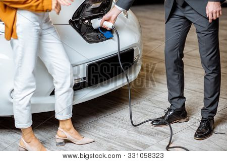 Sales Manager Showing How To Charge Electric Car To A Young Client, Plugging Wire Into The Car Socke