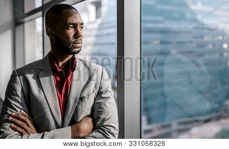 Confident Black African Businessman Standing With His Arms Crossed Looking Out The Office Window In