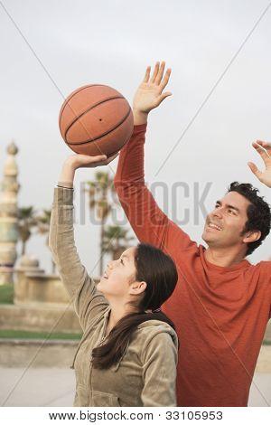 Hispanic father and daughter playing basketball