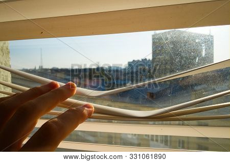Young Man Watching Through Plastic Blinds Windows Ot The Street. Close Up Hand Open Jalousie To Look