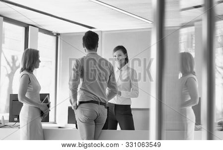Black and white photo of business people waiting while talking to receptionist in office lobby