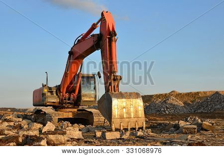 Large Tracked Excavator Works In A Gravel Pit. Salvaging And Recycling Building And Construction Mat